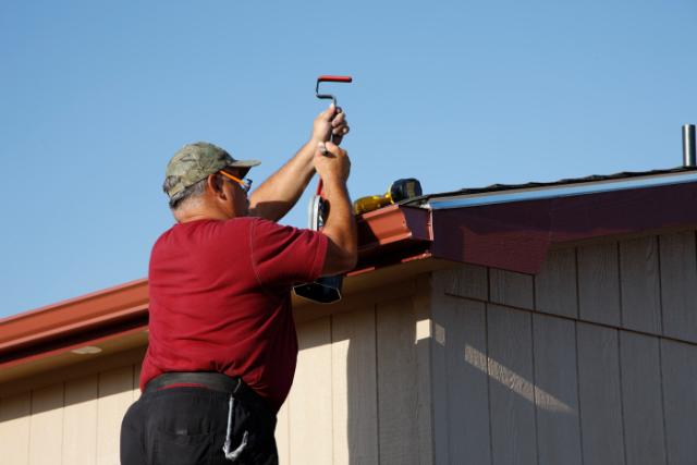 Beaverton Gutter worker Installing Downspout and Seamless Gutters
