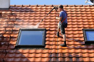 Beaverton worker doing a roof cleaning with high pressure washer