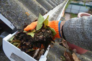Beaverton worker cleaning gutter