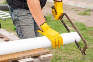 Worker cutting gutter pipe for Eugene Gutter Service